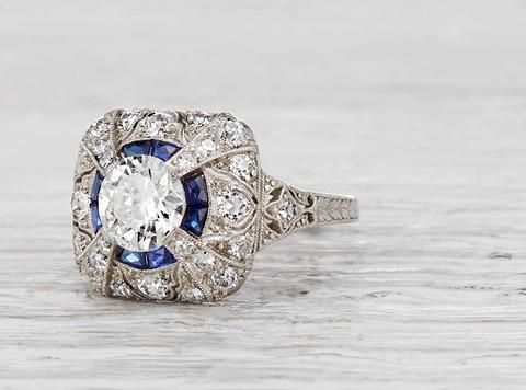 Antique Edwardian ring made in platinum and centered with an approximately .85 carat EGL certified old European cut diamond with E-F color and SI2 clarity. Accented with single cut diamonds and sapphires. Circa 1915. The ornate details of this ring are exquisite, and represent the pinnacle of Edwardian artistry and design. Diamond and gold mining has caused devastation in areas such as Africa, wreaking havoc on delicate ecosystems and communities. Choosing to go vintage, you are eliminating…