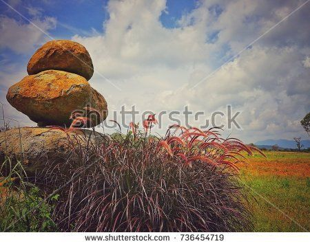 Stone Tower Zen Vintage Style with Purple Grass and Cloudy Sky Nature Image Background, Paksong Champasak Laos