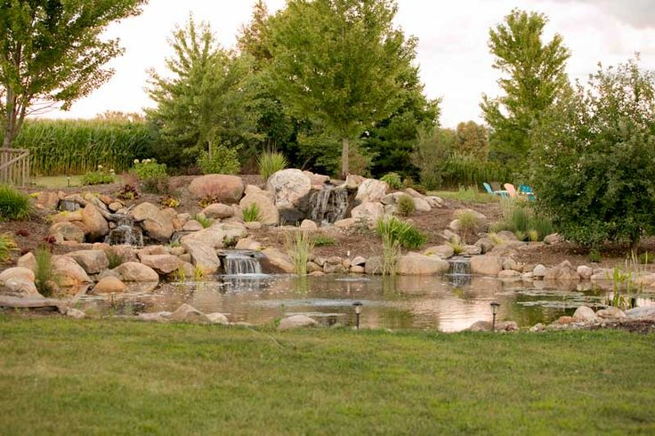 A large 35' x 35' pond with constructed wetland feeding a 20' stream. A 6000 series BioFalls® creates about a 4ft drop in the waterfall framed in two massive 1200 lb. boulders. This waterfall flows into a smaller pool area that feeds 2 cascading streams that have a combined flow of about 12,000 gallons per hour. A separate cascading stream flows from the constructed wetland with a 4,000 gallon an hour flow. A variable speed pump connects to 2 jets on the side to create some surface movement…