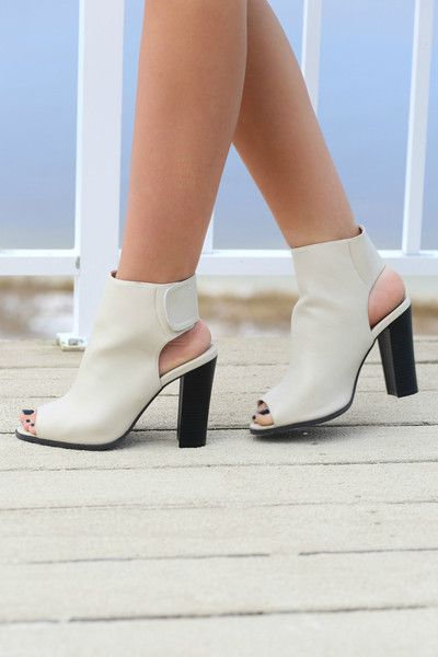 These booties are elevated on an ultra-high stacked block heel. They feature smooth synthetic leather, an open toe and a cutout heel. A wide hook-and-loop strap
