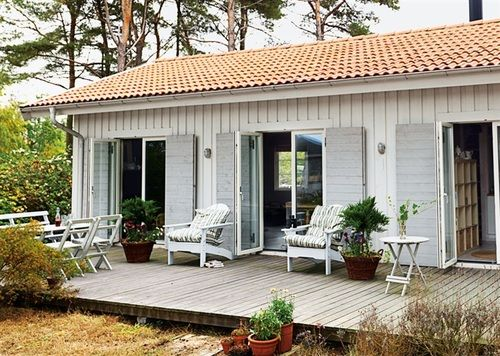 red roof . white facade . light shutters . wood deck .