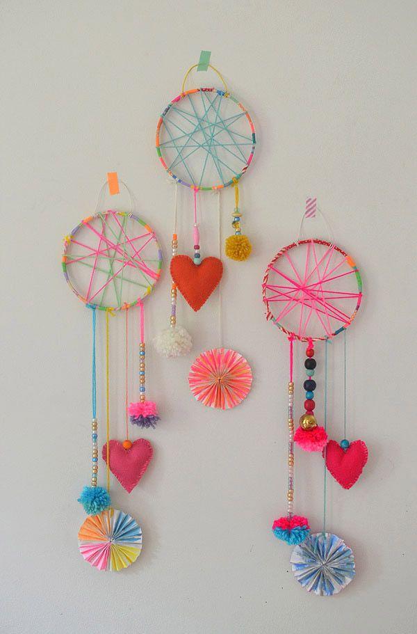 Atrapa sueños multicolores con corazones de tela y pompones de lanas de colores.