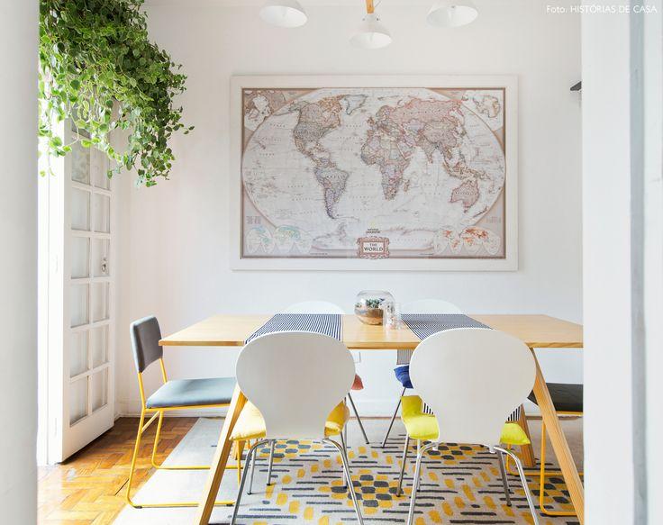 Sala de jantar tem mesa com tampo de pinus, cadeiras series 7 e prateleira alta com planta pendente.