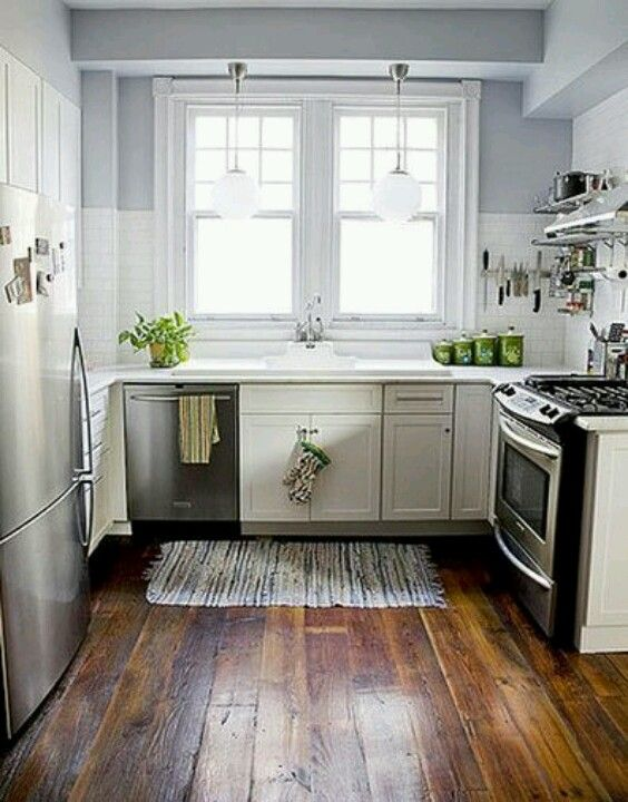 Soft gray walls, white subway tile, and white shaker kitchen cabinets offset by a rich wooden floor with a rustic undertone.