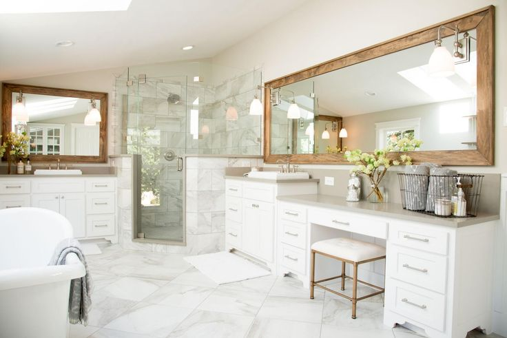 I loved the idea of marble tiles throughout this entire space. We also incorporated a fresh white wainscoting, light gray walls, and wood trimmed mirrors to warm the space up.