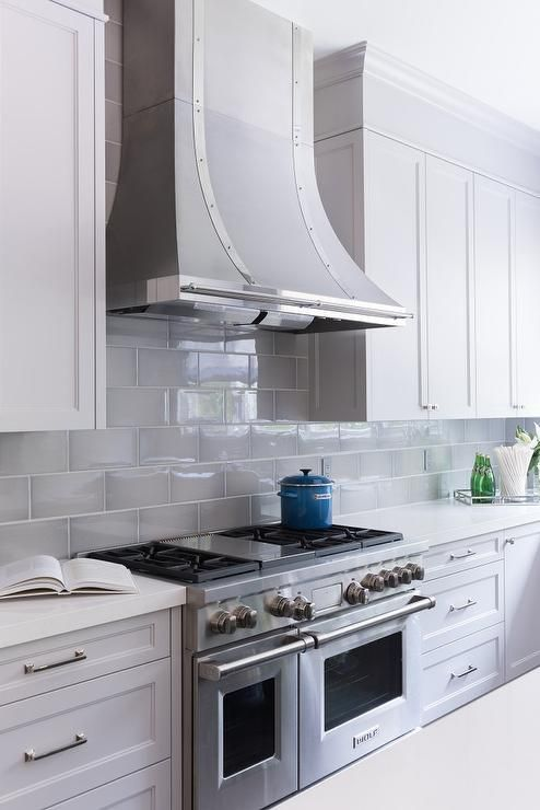 Beautiful kitchen boasts white shaker cabinets paired with white quartz countertops and a gray beveled subway tile backsplash.