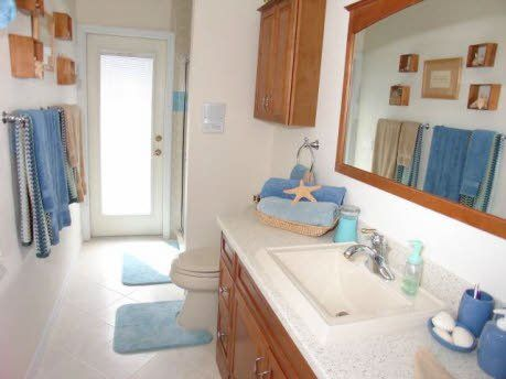 """Pool bathroom - can be closed off via pocket door to serve as """"en-suite"""" for the in-law suite at the rear of the house. Comfort height WC, a linen closet and maple cabinetry round this bathroom out!"""