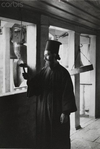 A monk sounds a gong in the Convent of Megaspelaeon-Fred Boissonnas
