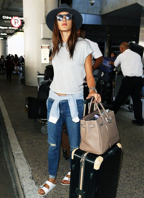 Alessandra Ambrosio wears a gray t-shirt, sweatshirt, boyfriend jeans, a fedora and white Birkenstocks