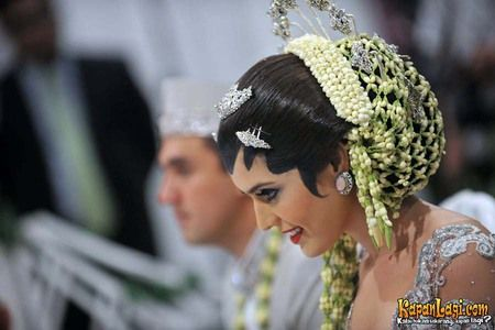 Sanggul gantung Carissa Putri ini terlihat cantik dengan hiasan dari jalinan bunga melati dan sedikit aksesoris perak di atas kepalanya.