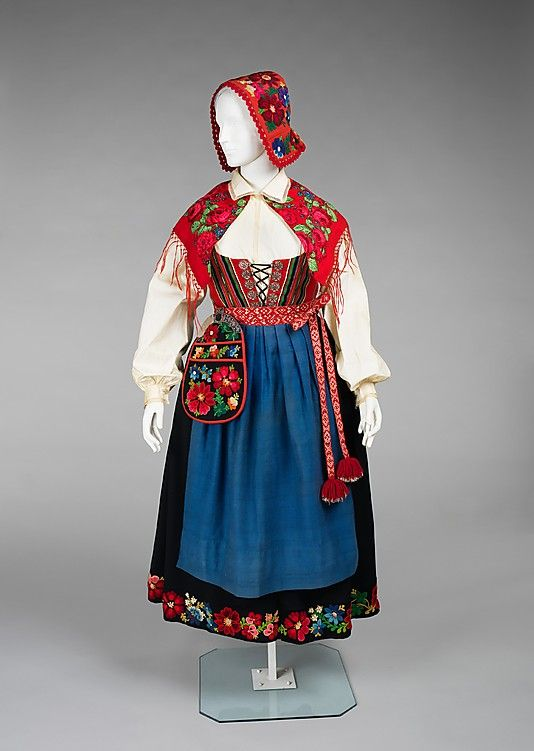 Ensemble, 1900–1915, Norwegian, wool, cotton, metal. This ensemble, known as a bunad represents the national dress of Norway. It is likely of the Rogaland variety, named for its district of origin. The form is based on traditions established in the 19th century. Bunads can be quite expensive due to the high quality of materials and craftsmanship in their construction. This example is evidence of this, especially in the handmade buttons and fine shirring of the skirt.