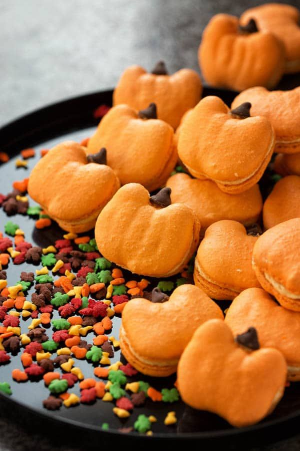 Celebrate fall with these adorable pumpkin macarons. Quick video tutorial and ton of tips on how to make pumpkin macarons are included.