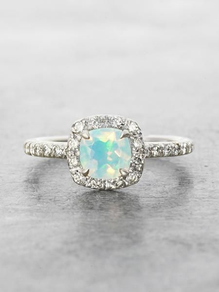 Flashing with Opalescent Rainbows, an ethereal 7mm cushion cut Ethiopian Opal is surrounded by a halo of Brilliant cut white VS Diamonds in this heavenly ring. Solid 14K White Gold. Handcrafted with L