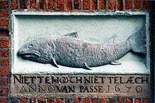 Gevelsteen van 'De Zalm' uit 1670 met de tekst: 'Niet te hooch niet te laech van passe.'
