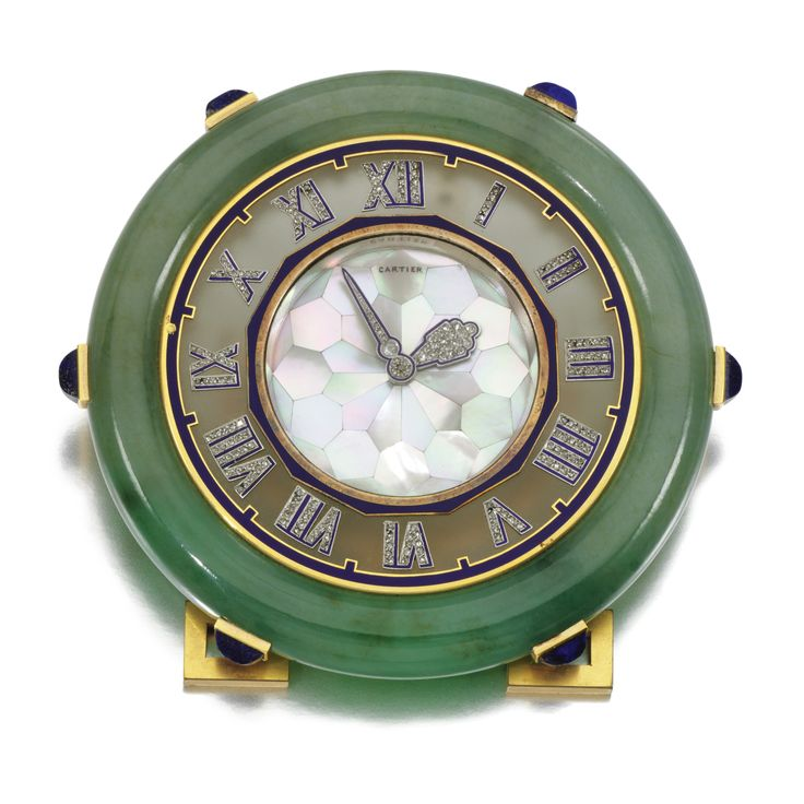 GEM-SET DESK CLOCK, CARTIER, CIRCA 1925  The circular dial inlaid with mother-of-pearl, royal blue enamel and diamond set hands, to a rock crystal bezel applied with Roman numerals, set within a jadeite frame, accented with sugarloaf lapis lazuli,