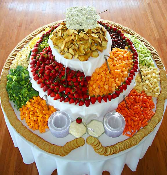 Awesome Fruit or Veggie Table Display for a Large Crowd. There must be a hula hoop, or something under the cloth to form a 'lip' so crackers and food do not get jostled off onto the ground/floor. If there isn't, the beautiful display will be an awful mess in no time!