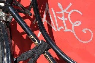 Black bike against a red backdrop with graffiti.