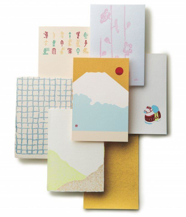 Various postcards called nengajo used for New Year's greetings in Japan. Designs often feature auspicious symbols and colors like Mount Fuji, zodiac animals, plum blossoms, and gold.