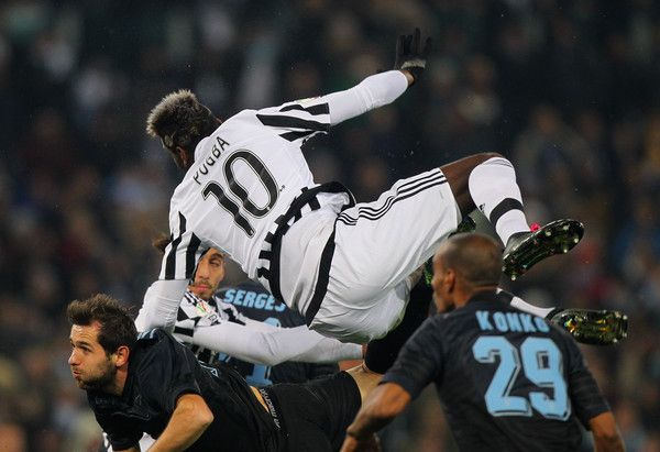 Paul Pogba Photos - Senad Lulic (L) of SS Lazio competes for the ball with Paul Pogba of Juventus FC during the TIM Cup match between SS Lazio and Juventus FC at Stadio Olimpico on January 20, 2015 in Rome, Italy. - SS Lazio v Juventus FC - TIM Cup