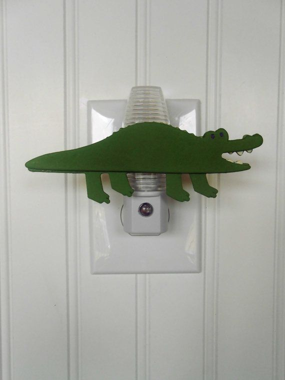 The alligator is made from wood. The night light is plastic with a sensor. This would be perfect for your baby nursery or for a boys room.    Night