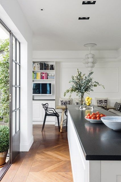 Elegant Modern Kitchen in modern kitchen design ideas - large white kitchen with long work surface, white walls and colour-coded cookbooks.