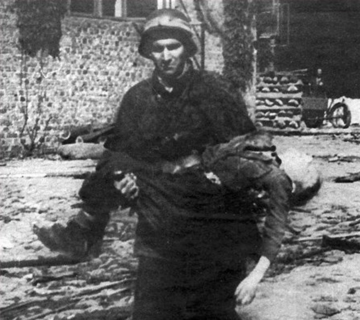 Ww2 • Polish Soldier carrying a dead body of a very young volunteer soldier who fell while fighting in the Warsaw Uprising. 1944 Warsaw Poland