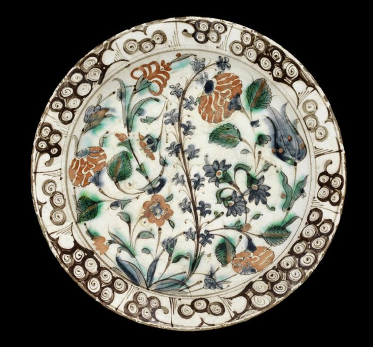 An Iznik 'Storm in a teacup' design pottery Dish Turkey, 17th Century with a sloping rim, underglaze, decorated in cobalt blue, raised red, green and black on a white background with carnations, tulips and prunus branch issuing from a leafy tuft, the rim with rock and wave design
