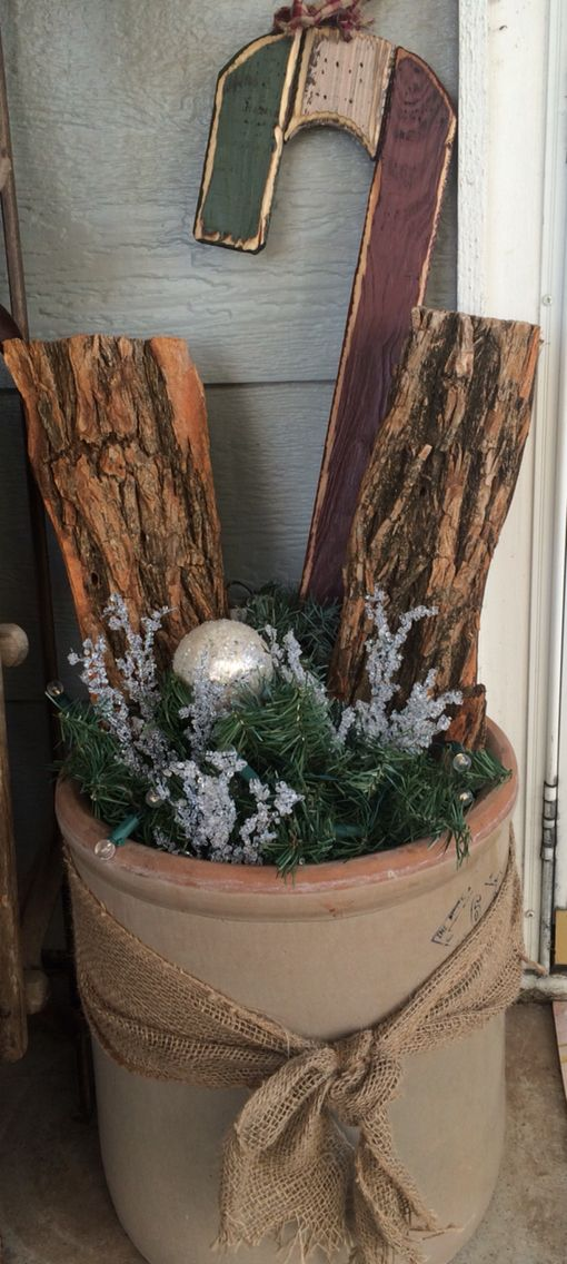 Christmas decor-couple of logs, some greenery, Christmas balls that look like snowballs, a cute candy cane and some battery operated battery all in a antique crock.
