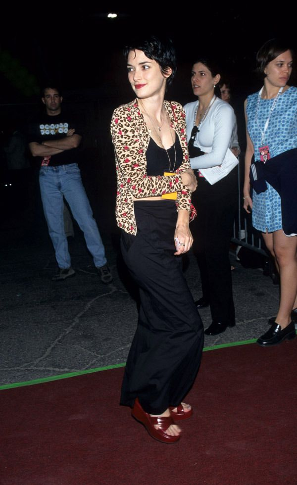 Winona Ryder's 12 Best '90s Outfits - In a look that screams '90s (in the best possible way), Ryder's wide-leg black pants and matching crop top, leopard cardigan and delicate necklaces in varying lengths wouldn't look out of place on a site like Nasty Gal today. FYI, Winona wore this ensemble to a U2 concert in 1997.