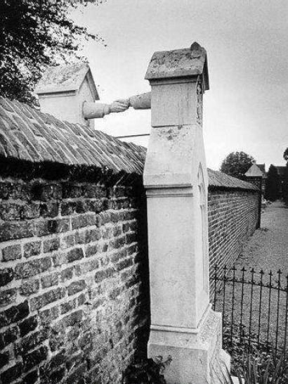 """Grave of a Catholic woman and her Protestant husband. The Protestant Colonel of Cavalry, JWC of Gorkum married the Catholic damsel JCPH of Aefferden. This """"mixed"""" marriage, at that time (the 19th century), would have given them trouble. The wife wanted to be buried next to her husband, but the difference in their denomination would not allow that. So the Colonel was buried in the Protestant part, against the separation wall and his wife was buried on the Catholic side."""