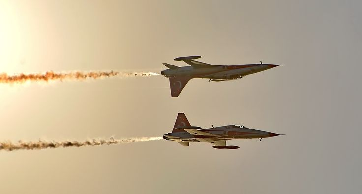 "two ""turkish stars"" f5 planes flying in close formation and one upside down with sun behind"