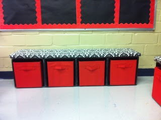 Milk crates zip-tied together on their sides so that a bench seat fits on top and red bins from Lowe's can slide inside them. NEED to make!