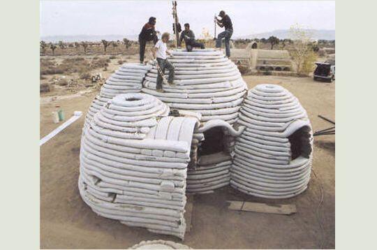 L'architecte américain Nader Khalili est à l'origine du Cal-Earth Institute (California Institute of Earth, Art and Architecture créé en 1991 dans le désert de Mojave,en Californie) qui concilie des objectifs humanitaire et écologique. Khalili, soucieux du sort du milliard de sans-abris, propose de leur construire un abri à base de sable et terre.