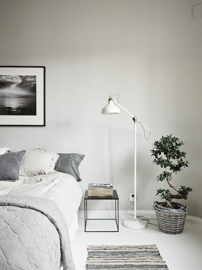 Bedroom: pale grey bed linen, white floor, white floor lamp, black square bedside table