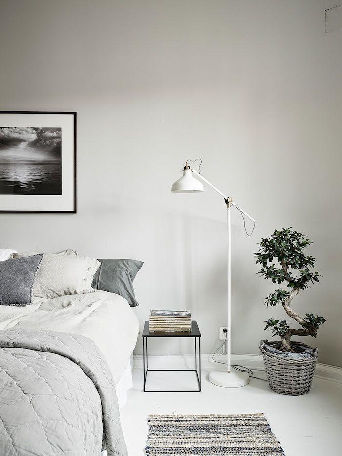 Bedroom: pale grey bed linen, white floor, white floor lamp, black square bedside table