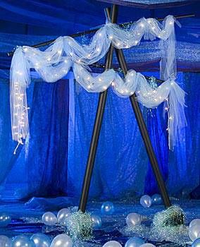 Your event room will look great with this Depths of Forever Arch. Each cardboard Depths of Forever Arch is 10 ft. high x 7 ft. wide and is accented with tulle, iridescent shred, and twinkle lights.