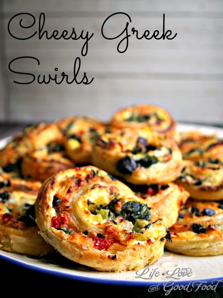Cheesy Green Swirls - tasty appetizer that starts with a frozen puff pastry and is layered with Feta, olives, spinach, and more Greek-inspired ingredients.