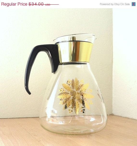 ~Krrb.com  Mod mid century vintage 1960s Pyrex Glass Carafe.  The perfect pitcher for coffee, tea or cool drinks in the summer.  Retro golden flowers and leaves on the glass. Finished with a golden neck and black handle.
