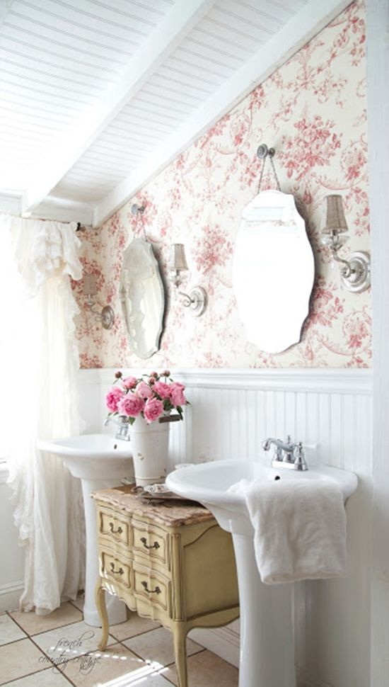 French Country style bathroom with toile wallpaper and scalloped mirrors over dual pedestal sinks design bathroom ideas home decor @lampsplus