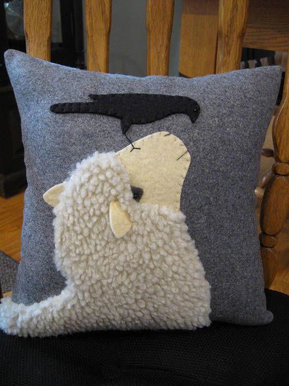 J'ai vu une photo similaire à cette scène et vient de tomber en amour avec elle! Telle une belle image et design touchante d'un mouton et de vol à la recherche à l'autre.  J'ai utilisé un tissu laineux pour le mouton et ajouté le visage et les oreilles dans un feutre de laine de couleur crème. Les oreilles sont en 3 dimensions. Le corbeau est fait en feutre de laine noir et il a une petite perle de rocaille pour un œil. J'ai cousu le motif sur un tissu de laine dans une couleur grise…