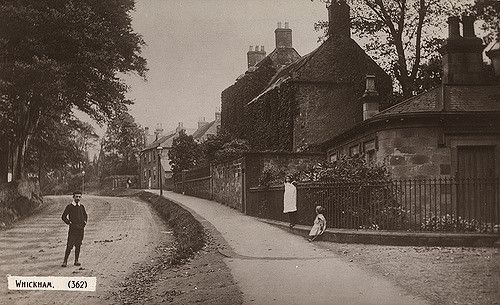 Type : Photograph Medium : Print-black-and-white Description : View of Whickham Front Street towards the east end with the gate of Whickham Lodge just out of shot to the right and housing in view.    Three children are in the shot one boy and two girls.  The photograph was taken in c1910. Collection : Local Studies Printed Copy : If you would like a printed copy of this image please contact Newcastle Libraries www.newcastle.gov.uk/tlt quoting Accession Number : 004274