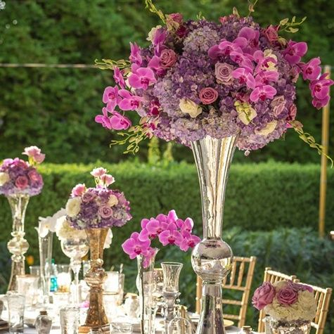High and low mercury-glass vases were filled with purple orchids, hydrangeas and mini calla lilies.  from the album: A Journey-themed Wedding in Adairsville, GA