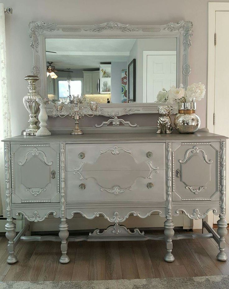 Beautiful vintage Jacobean buffet and mirror repurposed, upcycled and refinished!  White and gray chalk paint mixed with silver. The top all silver and silver gilding wax on all the details crystal glass knobs on the drawers original knobs on the doors.  Then completed the mirror for a gorgeous finish! You can see the before and more on my FB page ChicandShabbyFurnitureByRebecca
