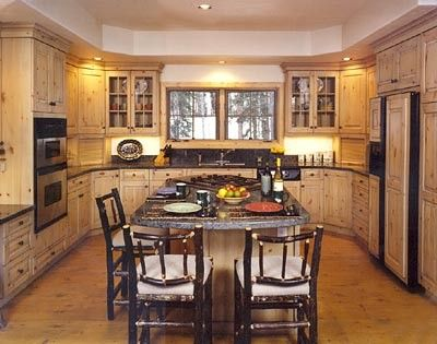 a u-shaped rustic kitchen with large island, cooktop, double wall oven and