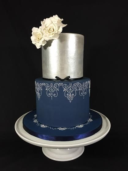 Elegant two-tiered royal blue and silver wedding cake. Hand-piped damask lace…