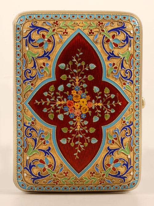 An exceptional Russian silver gilt and enamel cigarette case, Grachev, Moscow, circa 1890. Of rounded rectangle shape, the case is finely worked in multi-color cloisonne scrolling motif around a central shaped cartouche of deep red guilloche enamel enhanced with foliate sprays; gilded stippled grounds within a diapered turquoise enamel border. 88 silver standard.