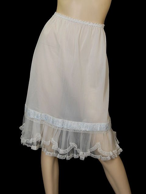 """Pretty white vintage Schiaparelli acetate slip with blue ribbon trim, lace, and ruffled chiffon scalloped hem. A great piece of design history! Waist: 24-30"""" Hips: up to 42"""" Total length: 24"""" CONDITIO"""
