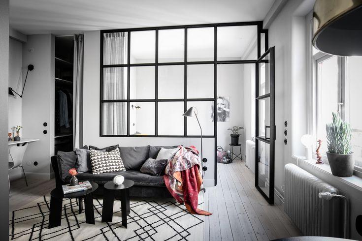 Спальня от гостиной отделена  выкрашенной в черный цвет рамой со стеклянными вставками и перегородка и окно и стенка