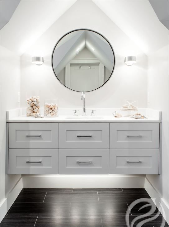 Exquisite bathroom features a nook with cathedral ceiling filled with a round metal mirror illuminated by modern polished nickel sconces and a gray floating washstand topped with white marble fitted with a stainless steel sink and a gooseneck faucet suspended over wood like tiled floors.