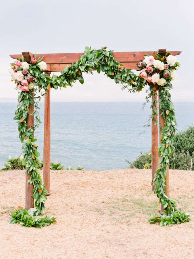 Beachy floral garland accented arbor: http://www.stylemepretty.com/california-weddings/goleta/2016/06/29/a-santa-barbara-wedding-that-epitomizes-california-cool/ | Photography: Michael + Anna Costa Photography - http://www.michaelandannacosta.com/